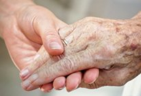 Older persons hand being held