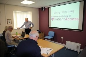 People at tables for training on patient access
